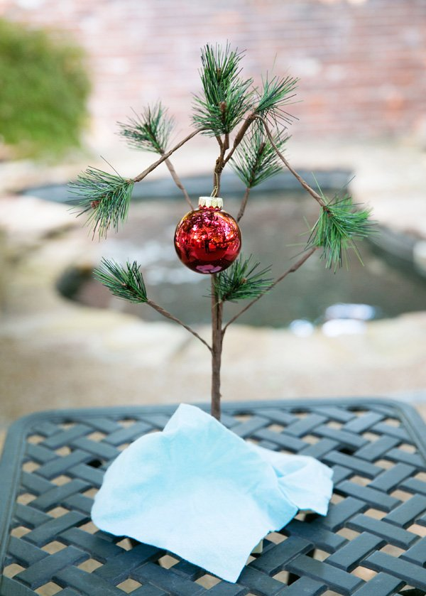 charlie brown christmas tree with red ornament and napkin skirt for a tacky christmas engagement party