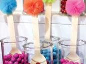 wooden spoons topped with poms in cases of multi colored gumballs