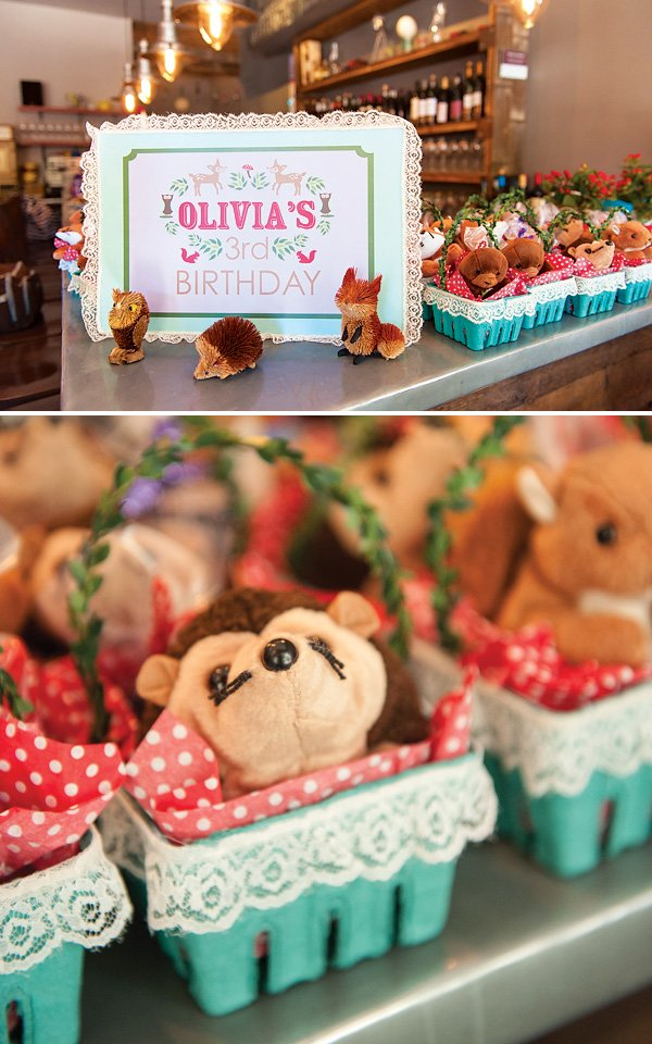 woodland birthday party favors with plush stuffed animals in baskets