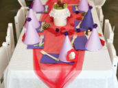 woodland birthday party kids table with purple party hats and eyelet cloth