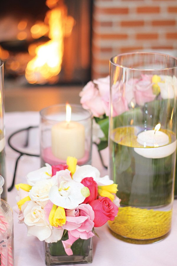 floating candle vases and small pink and yellow floral arrangement centerpieces