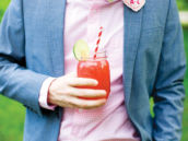 groom on his wedding day with a mason jar drink