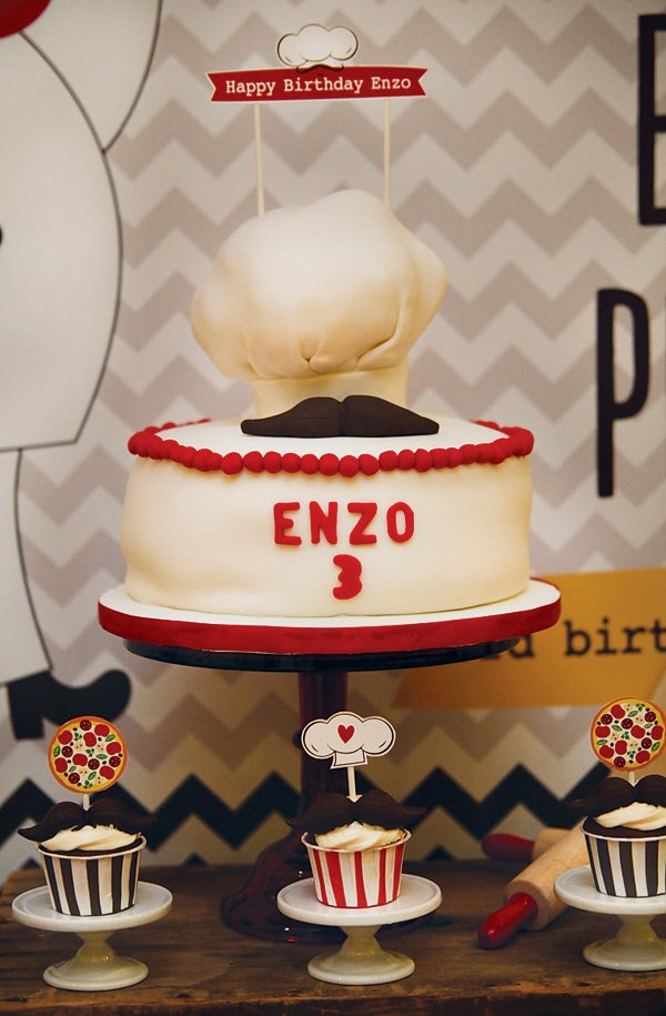 chef's hat and mustache topped birthday cake