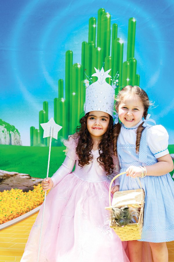 an emerald city backdrop and kid's wizard of oz costumes