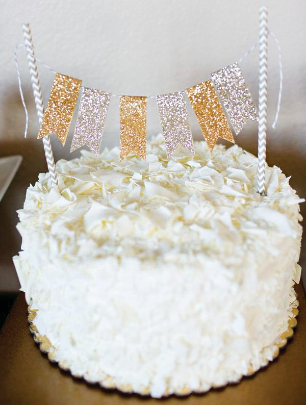 white chocolate shavings covered cake with mini glitter bunting