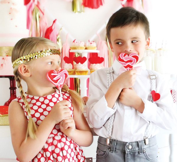 kid's valentine's day photoshoot with heart lollipops