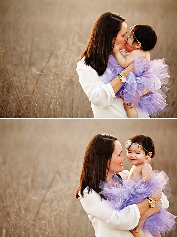 mom and baby daughter taking photos in a field