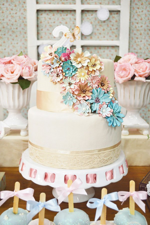 cascading pastel flowers and lace wrapped birthday cake