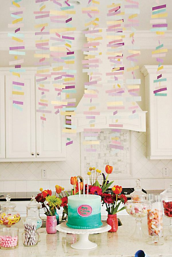 pink and purple confetti streamers above a birthday party's dessert table
