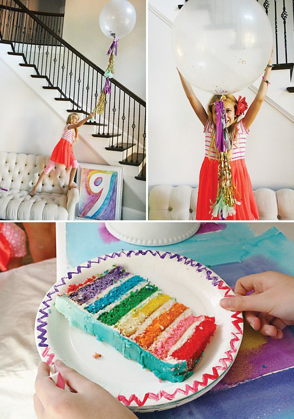 confetti filled party balloons and a rainbow layer birthday cake