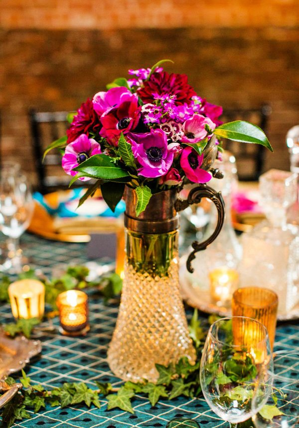 crystal pitcher of pink and purple orchids and flower centerpiece