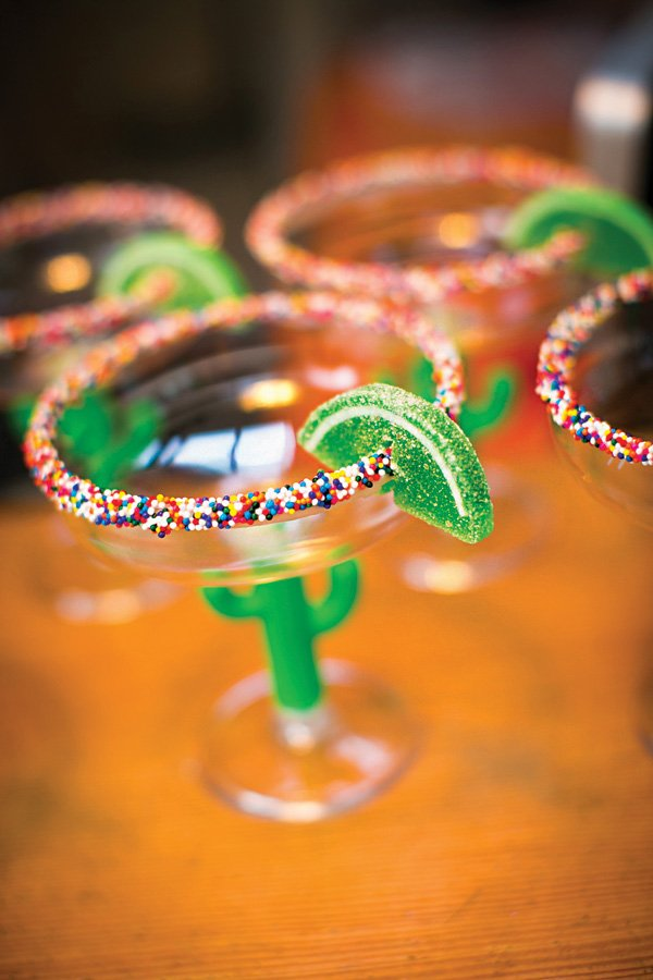 DIY candy margarita glasses with a sprinkled rim and gummy lime