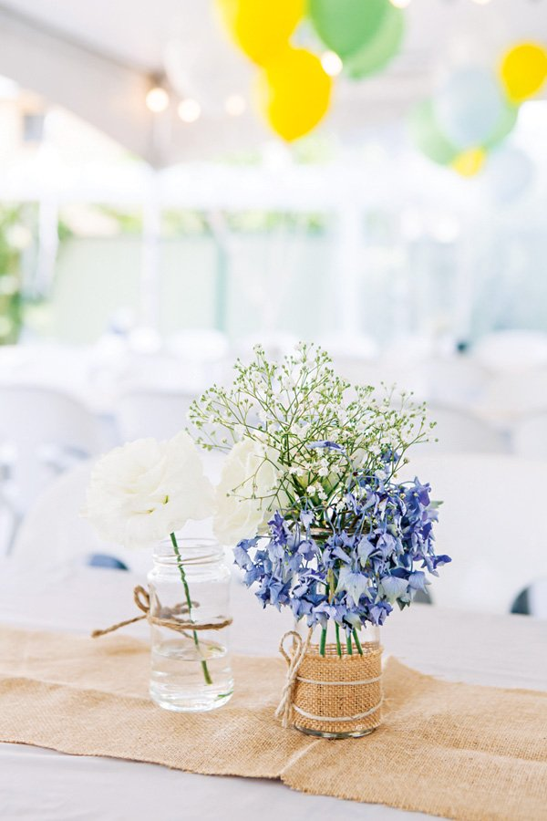 hydrangea and baby's breath floral arrangements and burlap table runner