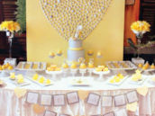 yellow and gray dessert table with a silver seashell heart backdrop
