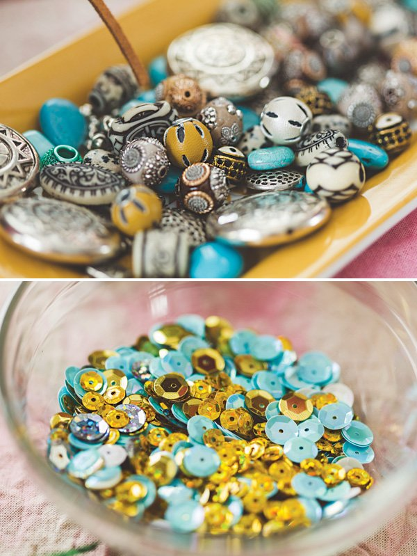 these blue and gold beads and sequins are supplies for crafting