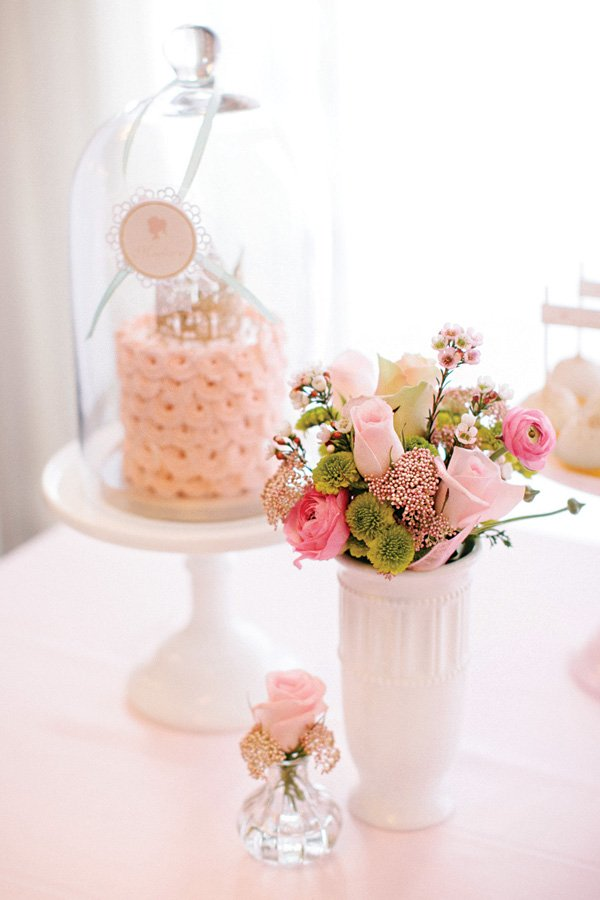 pink floral arrangement and glass cake dome