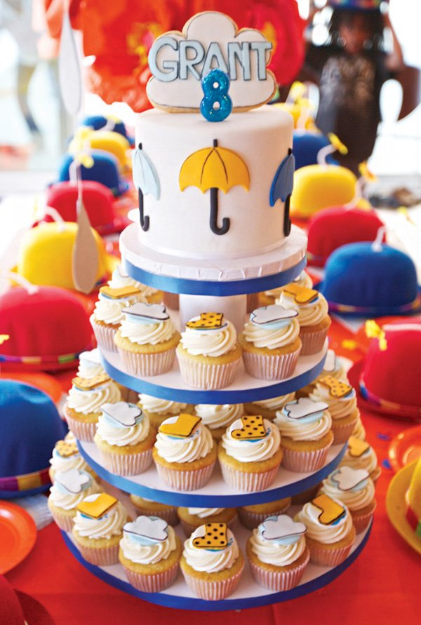raincloud topped umbrella birthday cake and rain boot topped cupcakes