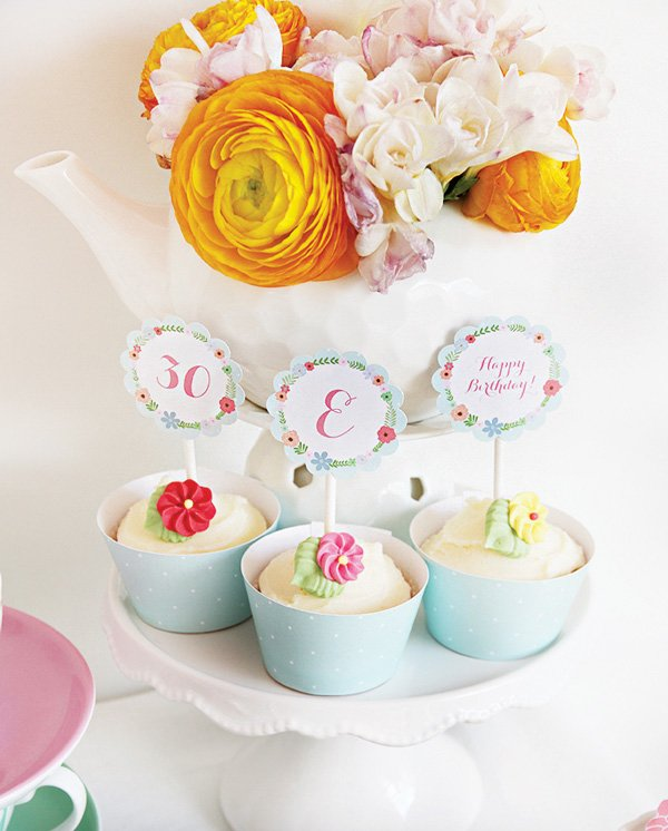 flower topped cupcakes and a white teapot floral vase centerpiece