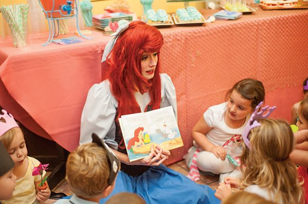 ariel from the little mermaid reads a story at a party