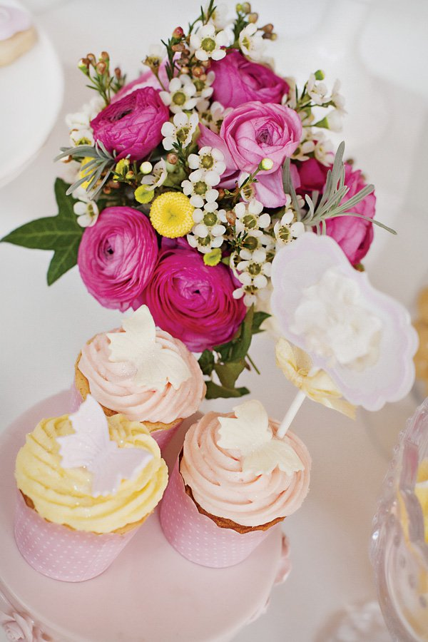 bright pink peony floral arrangement and butterfly cupcakes