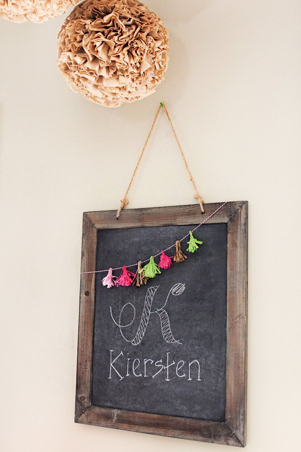 mini tassel garland on a chalkboard sign
