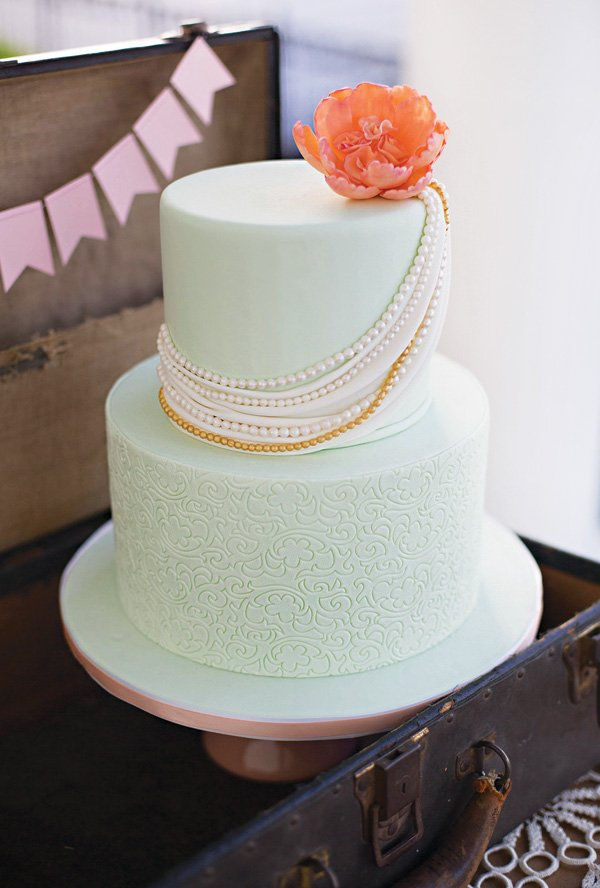 pearl draped mint wedding cake with a coral flower topper