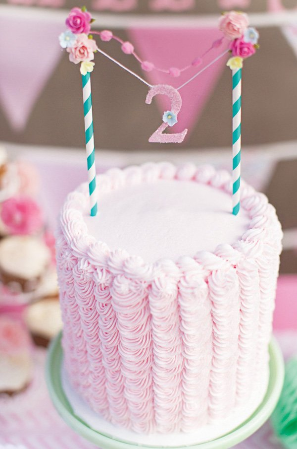 sweet pink cake with a mini flower bunting topper