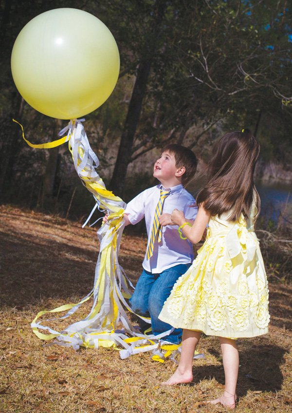 large yellow balloon and white and yellow tassels