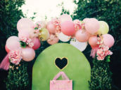 diy pink balloon and flower arch over a cardboard doorway