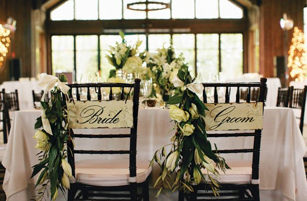 green and white floral decorated bride and groom chairs