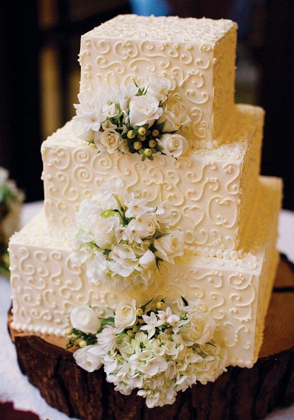 simple white swirl and flowers wedding cake