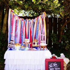 country tea party dessert table with ripped fabric backdrop