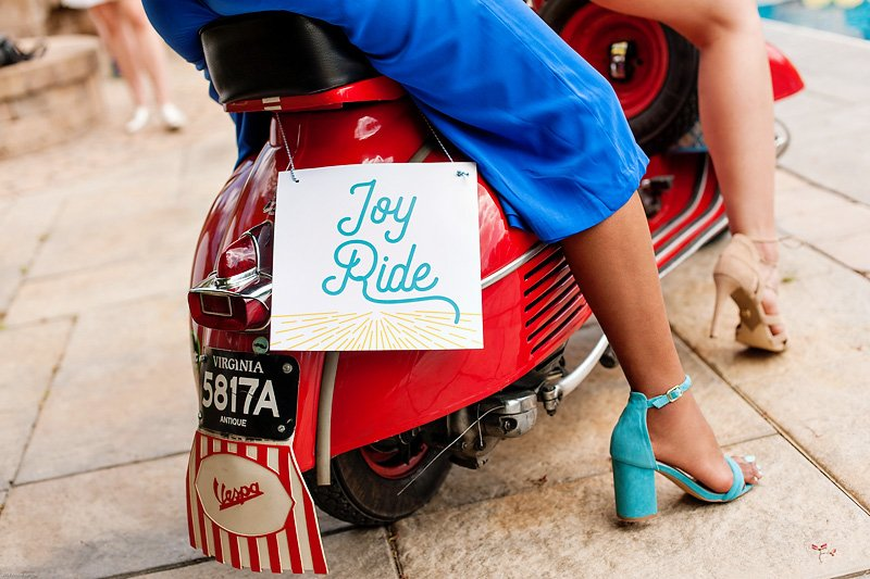 red vespa and joy ride sign