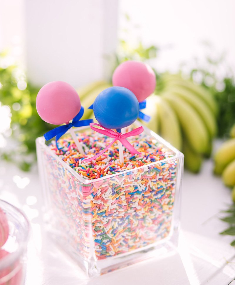 pink and blue cake pops in sprinkles vase